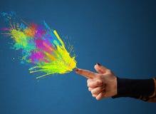 Красочный брызгает приходите из рук сформированных оружием Стоковые Фото