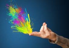 Красочный брызгает приходите из рук сформированных оружием Стоковое Изображение