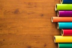 Красочный винил свертывает на деревянной предпосылке Стоковое фото RF