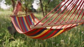 Красочный гамак протягиванный между деревьями в саде Пестротканый striped гамак вися в саде между видеоматериал
