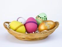Красочный дизайн пасхального яйца на бамбуковой корзине на белой предпосылке Стоковые Фотографии RF