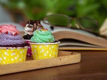 Красочный домодельного пирожного на деревянном подносе дальше и открытой книге на деревянном столе Концепция образа жизни и ослаб Стоковая Фотография