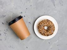 Красочный донут и коричневый бумажный стаканчик на серой конкретной предпосылке, конце вверх, взгляд сверху Концепция пекарни, св стоковое изображение rf