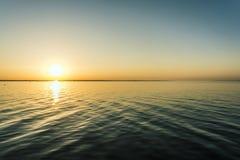 Красочный заход солнца над поверхностью воды, выравнивая солнце над заливом, небо лета без облаков стоковые фотографии rf