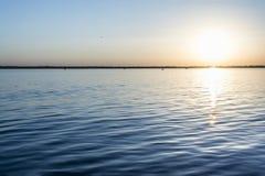 Красочный заход солнца над поверхностью воды, выравнивая солнце над заливом, небо лета без облаков стоковое фото rf