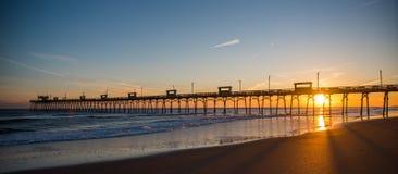 Красочный заход солнца на побережье океана с силуэтом пристани и фото Стоковые Изображения