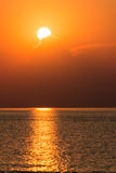 Красочный заход солнца в море с отражениями и облаками Стоковое Фото