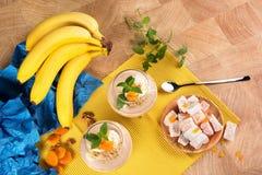 Красочный комплект бананов, турецкого наслаждения, высушенных абрикосов, и сладостных десертов плодоовощ на светлой деревянной пр Стоковые Изображения