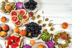 Красочный комплект плодоовощ фиолетовой, красной и оранжевой предпосылки в шарах Слива, персики, арбуз отрезанный над белой столе Стоковые Изображения RF
