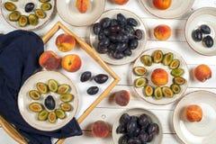 Красочный комплект плодоовощ фиолетовой, красной и оранжевой предпосылки в шарах Слива, персики, арбуз отрезанный над белой столе Стоковые Фото