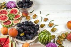 Красочный комплект плодоовощ фиолетовой, красной и оранжевой предпосылки в шарах Слива, персики, арбуз отрезанный над белой столе Стоковая Фотография RF