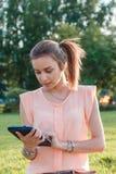 Красочный конец вверх девушки используя таблетку в парке Стоковое Фото