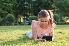 Красочный конец вверх девушки используя таблетку в парке Стоковые Фото