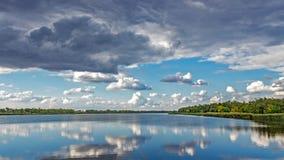 Красочный лес с зелеными желтыми деревьями и небом идти дождь отразил в озере поверхности воды, реке Солнечное небо с серыми обла Стоковые Фотографии RF