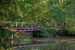 Красочный мост над потоком в уютном парке Стоковая Фотография
