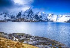 Красочный пейзаж островов Lofoten с группой в составе дома против гор Snowy Стоковая Фотография RF