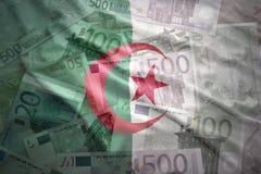 Красочный развевая алжирский флаг на предпосылке евро Стоковые Фото