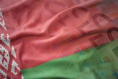 Красочный развевая национальный флаг Беларуси на предпосылке банкнот денег евро Стоковое Изображение RF