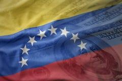 красочный развевая национальный флаг Венесуэлы на предпосылке денег доллара финансы яичка диетпитания принципиальной схемы предпо Стоковое Изображение RF