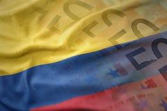 Красочный развевая национальный флаг Колумбии на предпосылке банкнот денег евро Стоковое фото RF