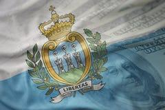 Красочный развевая национальный флаг Сан-Марино на американской предпосылке денег доллара Стоковая Фотография RF