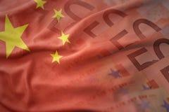 Красочный развевая национальный флаг фарфора на предпосылке банкнот денег евро Стоковое Изображение