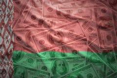 Красочный развевая флаг Беларуси на предпосылке денег доллара Стоковые Фото