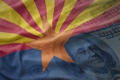Красочный развевая флаг положения Аризоны на американской предпосылке денег доллара стоковые изображения
