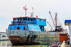 Красочный ржавый корабль в гавани Джакарты с рыболовами на борту стоковые фото