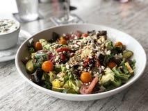 Красочный салат с arugula, козий сыром, красным луком, желтыми томатами, красными перцами, огурцом, авокадоом, грибами и бальзами Стоковые Изображения
