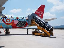 Красочный самолет пассажира с пандусом восхождения на борт на рисберм стоковое фото