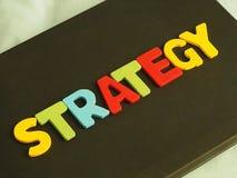 Красочный слова стратегии на черной предпосылке забастовщик стратегии удерживания руки принципиальной схемы бизнесмена дела бейсб Стоковые Изображения