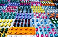 Красочный таблеток и пилюльки капсул в упаковке волдыря аранжировал с красивой картиной Концепция фармацевтической промышленности стоковое фото