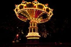 Красочный цепной carousel качания в движении на парке атракционов на ноче Стоковое Изображение