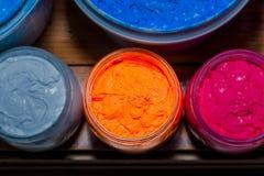 Красочный чернил пластизоля в ясном стекле смогите на таблице сосновой древесины для футболки печати экрана стоковое фото