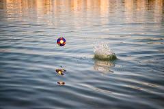 Красочный шарик игрушки, атрибут футбольной игры отражая в волнистой воде Стоковое Изображение RF