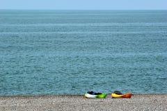 2 красочных каяка моря с затворами и спасательными жилетами на каменистом пляже Стоковое фото RF