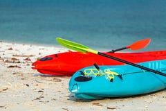 2 красочных каяка на пляже с зеленой маской подныривания Стоковые Фото