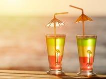 2 красочных коктеиля в заходе солнца на предпосылке моря, конец вверх Стоковое Изображение RF