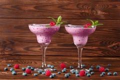 2 красочных коктеиля smoothie в стеклах маргариты на деревянной предпосылке Освежая напитки с зрелыми яркими ягодами Стоковые Изображения