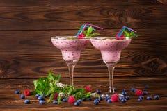2 красочных коктеиля smoothie в стеклах маргариты с яркими соломами Освежая напитки с зрелыми ягодами скопируйте космос Стоковые Фото