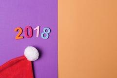 2018 красочных номеров и шляпа santa на бумажном backround, минимальном стиле Стоковое фото RF