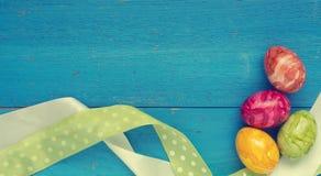 4 красочных пасхального яйца на голубой древесине Стоковая Фотография