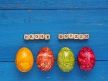 4 красочных пасхального яйца на голубой древесине Стоковые Фото