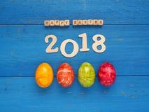 4 красочных пасхального яйца на голубой древесине Стоковое Изображение RF