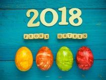 4 красочных пасхального яйца на голубой древесине Стоковые Фотографии RF