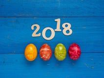 4 красочных пасхального яйца на голубой древесине Стоковое Изображение