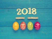 4 красочных пасхального яйца на голубой древесине Стоковое фото RF