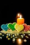 4 красочных печенья сердца с тестом печенья и свечой, в f Стоковые Изображения