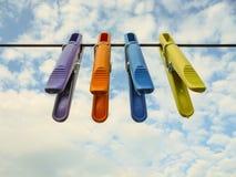 4 красочных пластиковых зажимки для белья вися от веревочки стоковое изображение rf